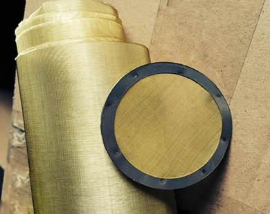 A roll of brass wire mesh and a round brass filter disc with rubber wrapping edge are placed together.