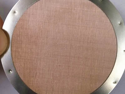 A hand is holding a piece of copper wire mesh filter disc with stainless steel edge.