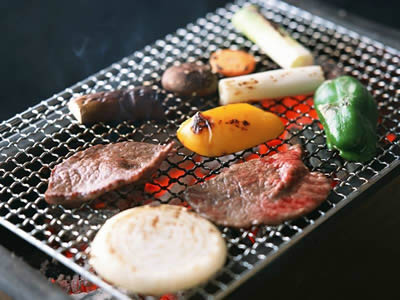 There is a barbecue grill made of crimped wire mesh with meats and vegetables on it.