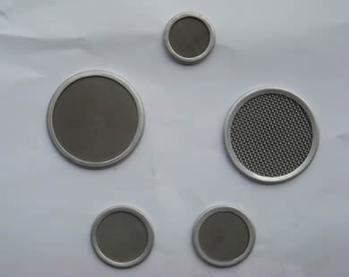 Five round stainless steel filter discs with different sizes.