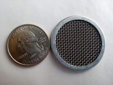 A multi-layer filter disc with wrapping edge is beside a metal coin.