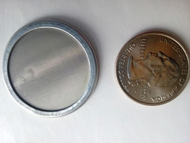 A ultra fine wire woven stainless steel is beside a metal coin.