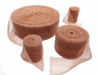 Four rolls of copper knitted mesh in different diameters on the ground.