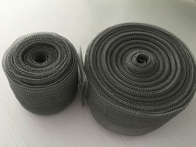 Two rolls of flattened surface knitted mesh on the table.