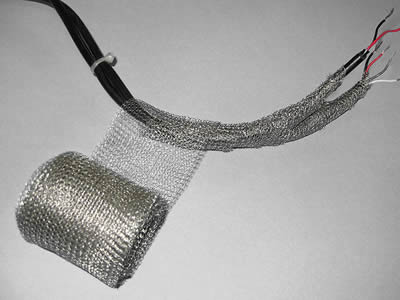 A roll of stainless steel knitted mesh is wrapping the cables.
