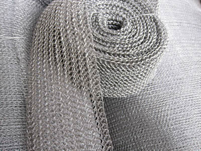 A roll of stainless steel knitted mesh with multi-filament wires on the knitted mesh pad.