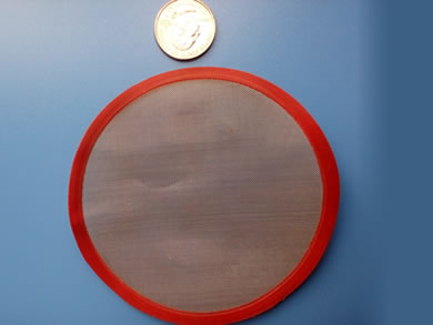 A round stainless steel filter disc with red painting edge is beside a metal coin.