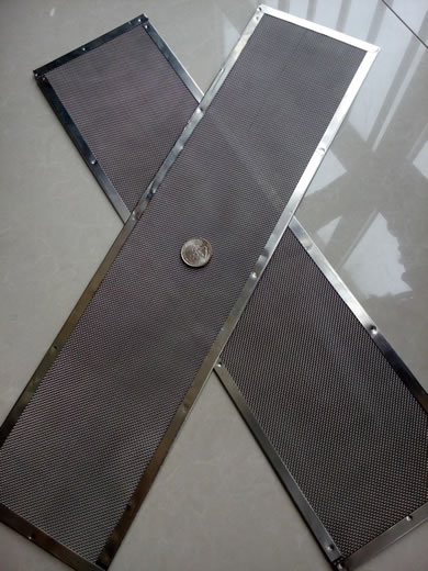 Two pieces of stainless steel filter disc in rectangular shape are crossed together with a metal coin in the middle.