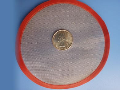 A round stainless steel filter disc with red painting edge is under a metal coin.