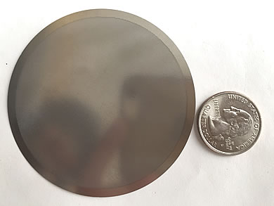 A round filter disc with shiny and smooth surface is beside a metal coin.