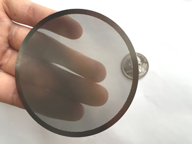 A hand is touching a translucent filter disc.