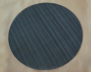 A round twill weave black wire cloth filter disc.